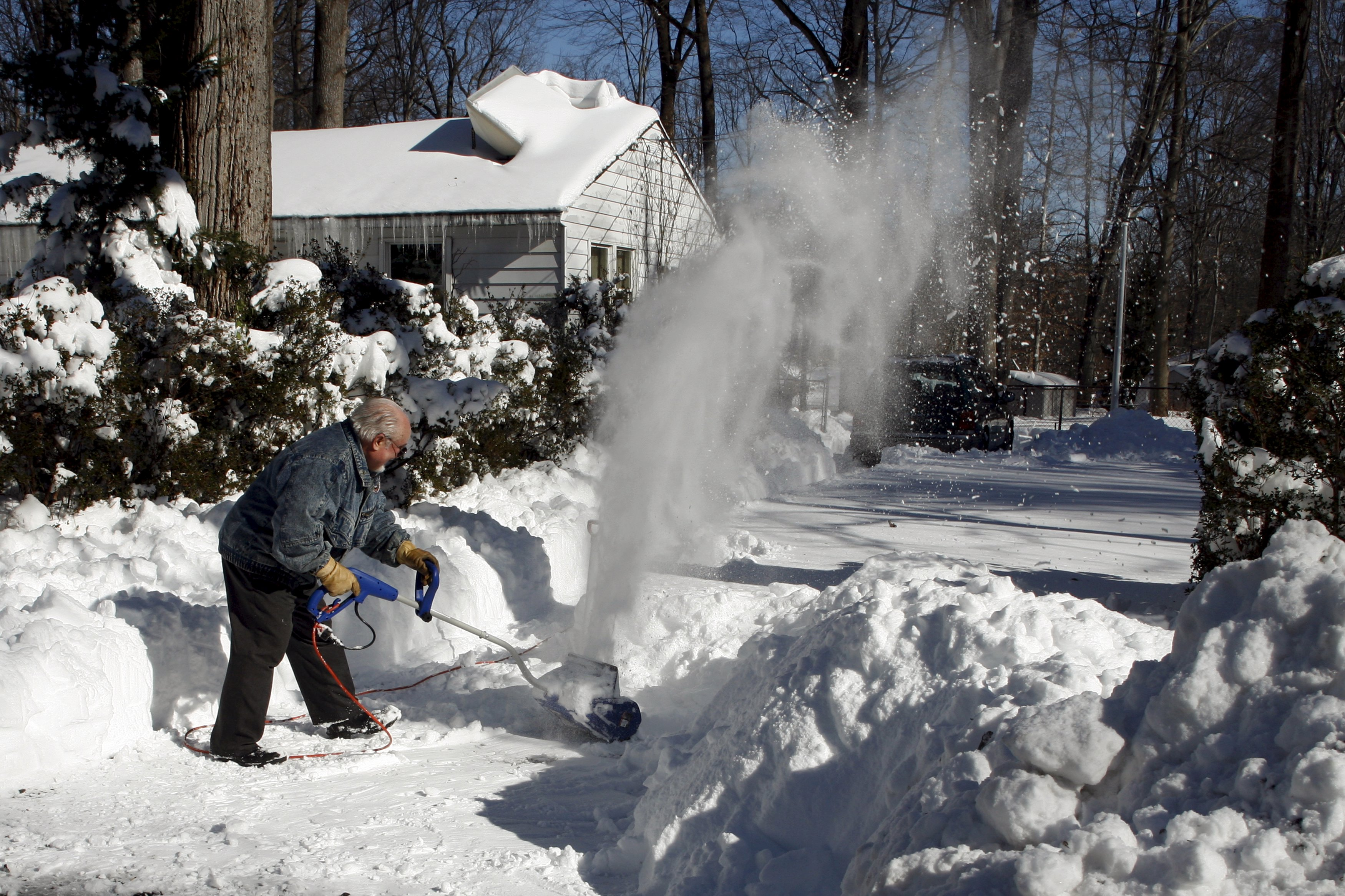 A man clears away snow in his front yard. The blizzard dumped up to 26 inches of snow in New York and Washington D.C. Photo: Reuters