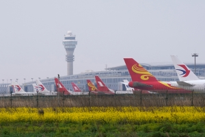 China orders sharp cuts in airline flights to curb virus risk