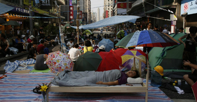 A protester sleeps in his own bed in Nathan Road as other demonstrators continue their sit-in. Photo: RTHK
