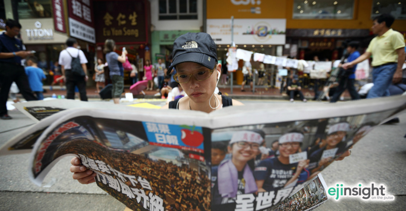 A pro-democracy activist reads Apple Daily at the height of the Occupy protests last year. Photo: Bloomberg