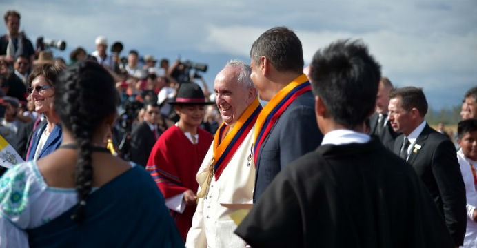 Pope Francis (in white) is escorted by Rafael Correa upon arriving in Ecuador. Photo: AFP