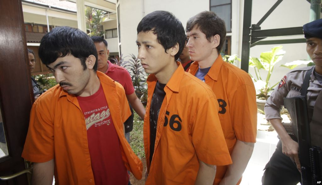 Abdulbasit Tuzer, Ahmet Mahmud and Abdullah (left to right) are escorted by police to their trial in Jakarta. They were found guilty of violating anti-terrorism and immigration laws. Photo: AP