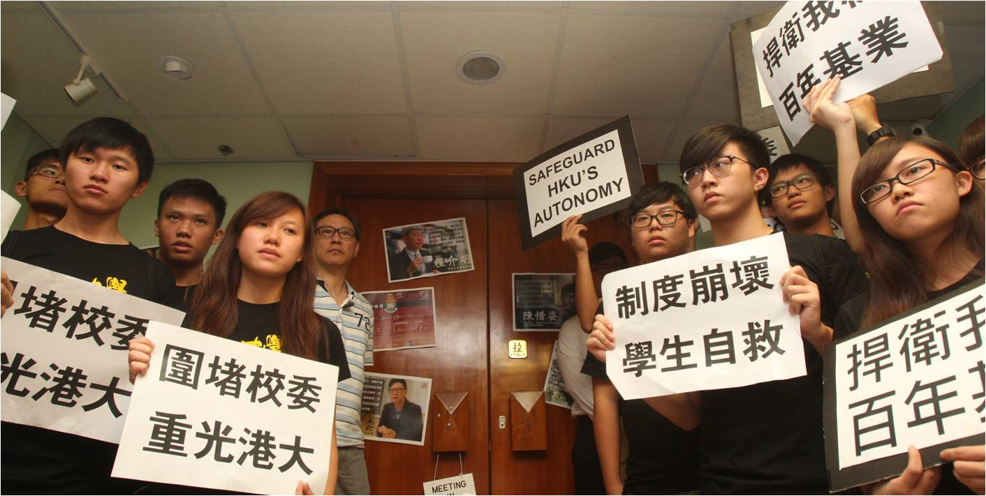 HKU students hold placards demanding academic freedom before a council meeting ended in chaos Tuesday. Photo: HKEJ