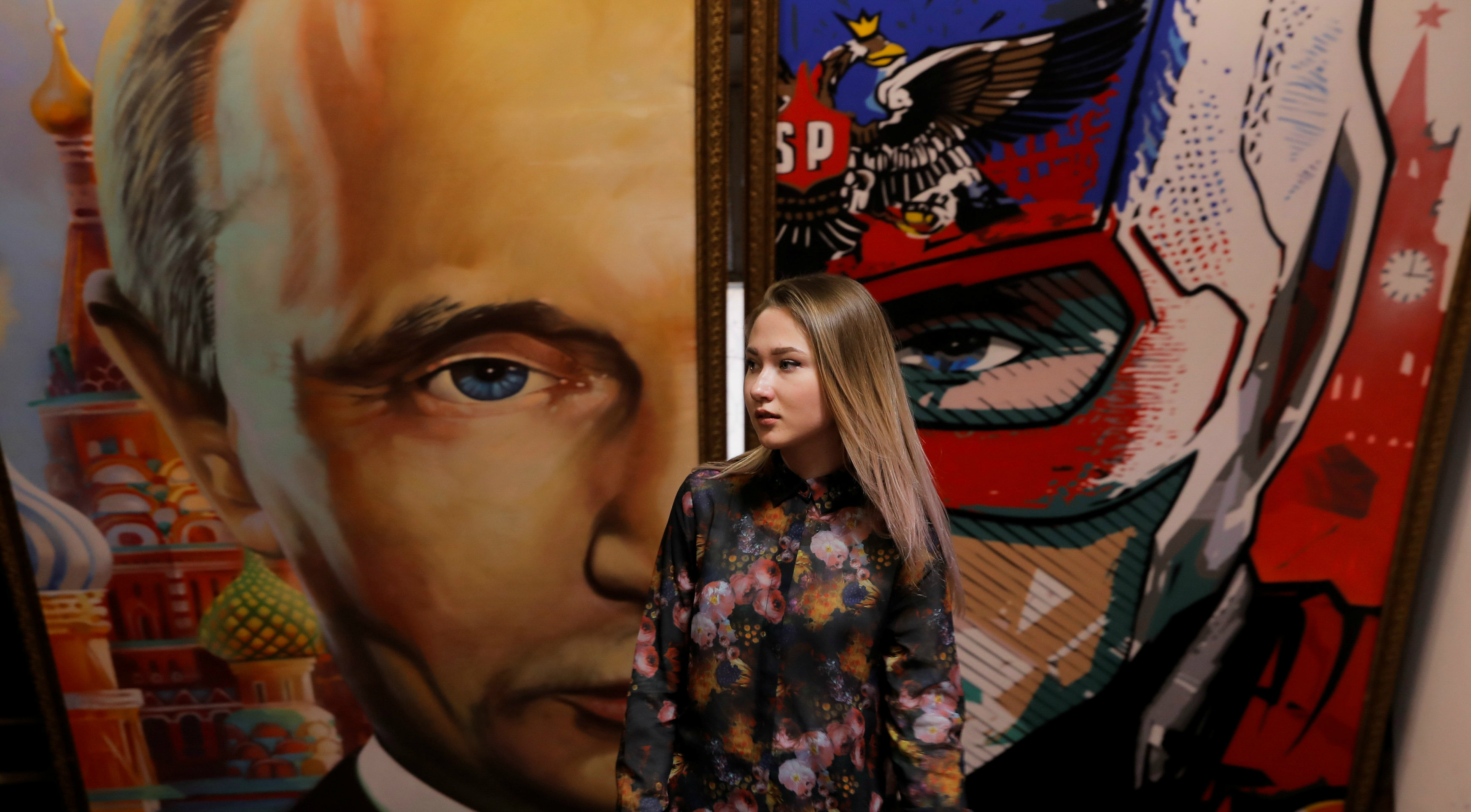 "A woman stands in front of a painting depicting Russian President Vladimir Putin at the ""SUPERPUTIN"" exhibition at UMAM museum in Moscow on Wednesday. Photo: Reuters"