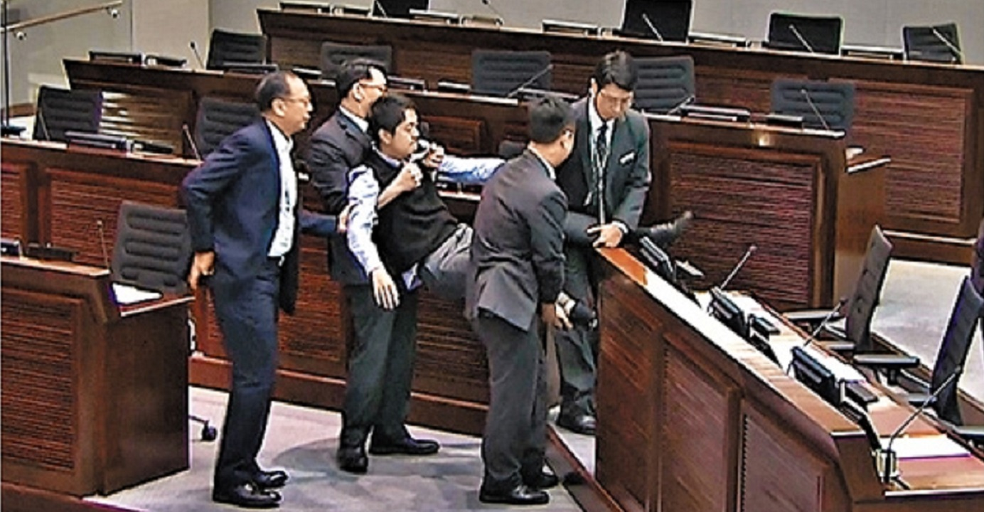 Democratic Party lawmaker Ted Hui is physically removed by security guards from a meeting of the committee on the national anthem bill on Monday. Photo: TVB News