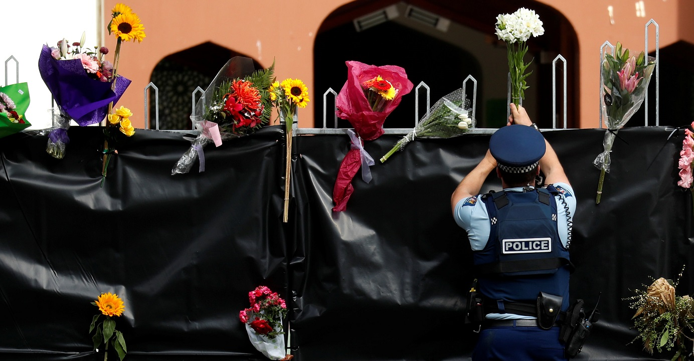 A police officer places flowers at the entrance of Masjid Al Noor in Christchurch, New Zealand on Sunday. Decision-makers around the world should closely stand by pluralism. Photo: Reuters