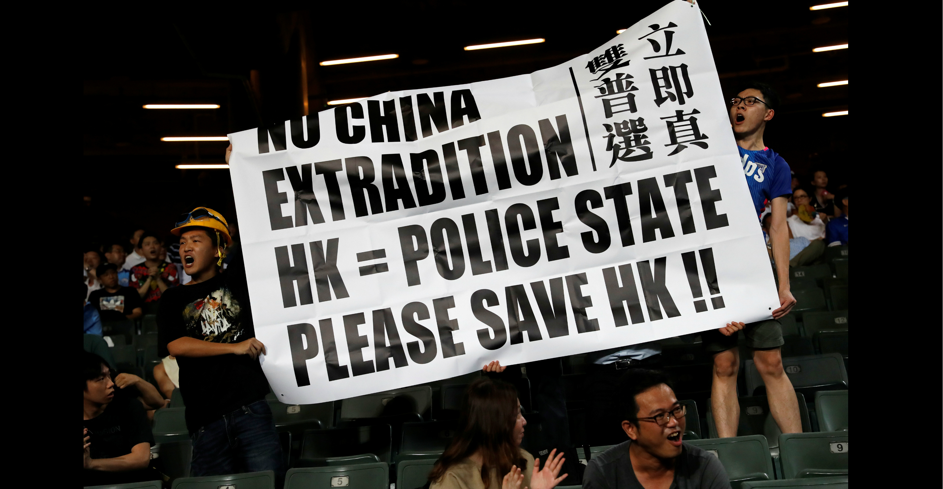 Fans hold an anti-extradition bill banner during a friendly match between Manchester City Football Club and Kitchee on Wednesday. Photo: Reuters