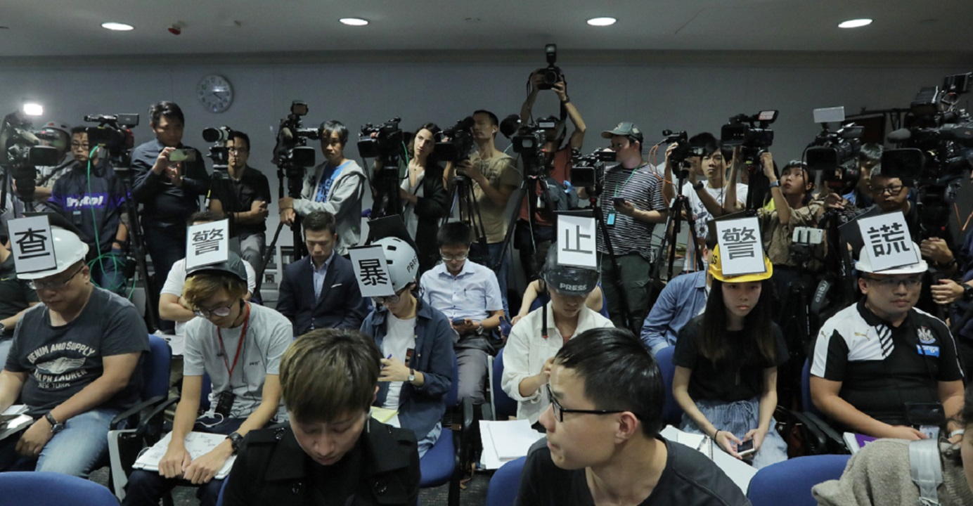 Six reporters stage a silent protest at the start of a regular police press briefing on Monday. Photo: HKEJ