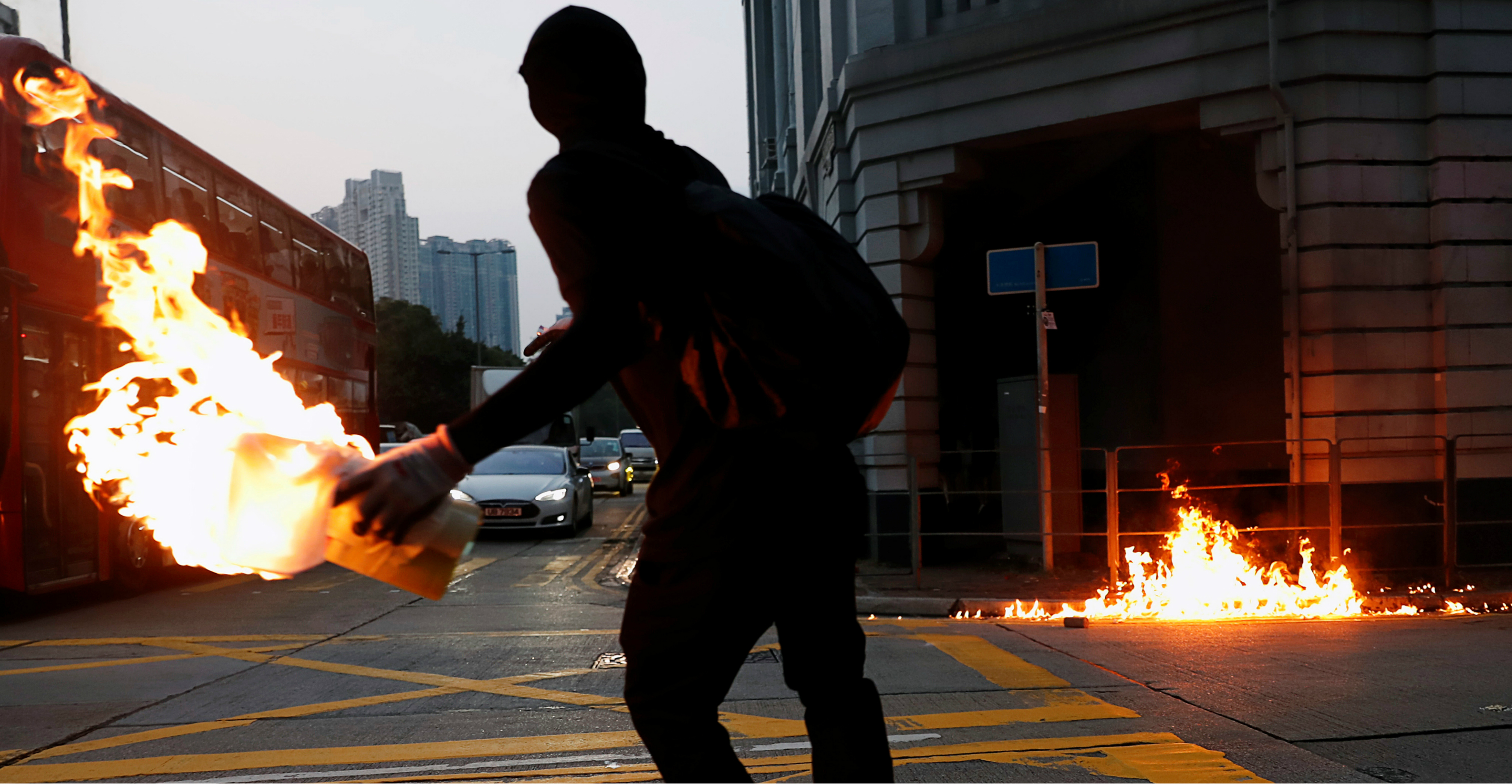 A black-clad protester hurls a petrol bomb at a police station in Sham Shui Po on Oct. 20. Photo: Reuters