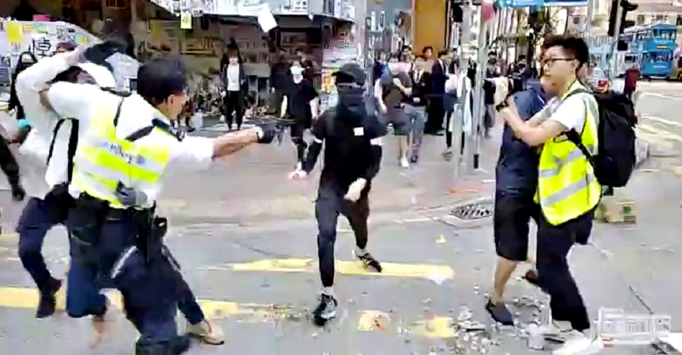 A still image from a social media video shows a police officer aiming his gun at a protester in Sai Wan Ho on Monday morning. Photo: Cupid Producer via Reuters