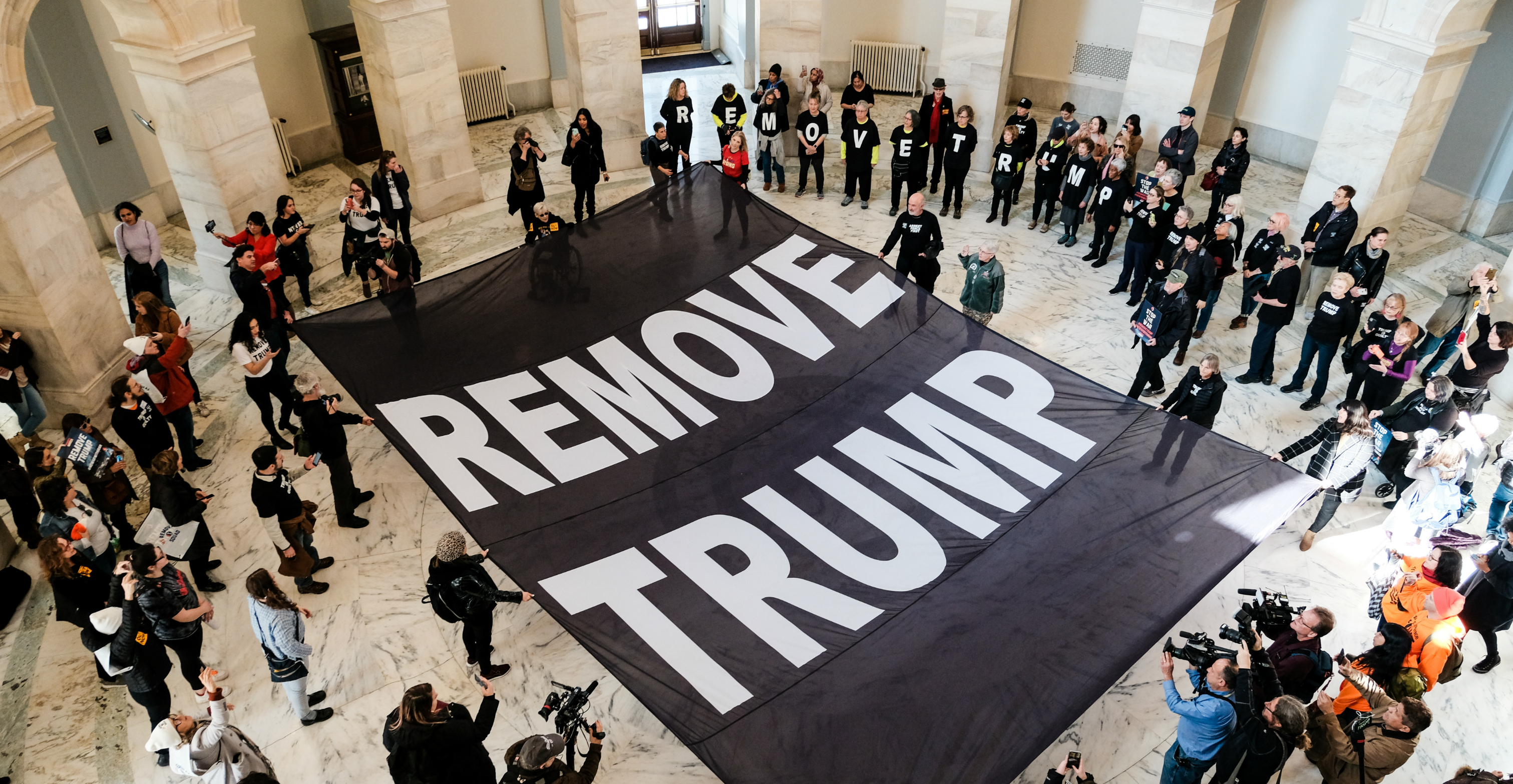 Activists spread out a banner calling for the removal of US President Donald Trump on the floor of the Russell Senate Office Building during a demonstration on Capitol Hill in Washington on Thursday. Photo: Reuters