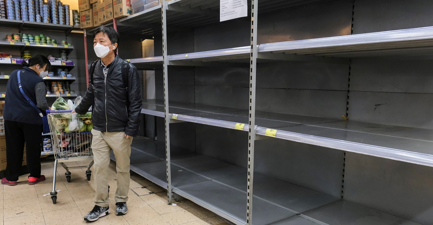 Customers wearing masks walk past empty shelves at a supermarket amid panic-buying in the wake of the novel coronavirus outbreak. Photo: Reuters