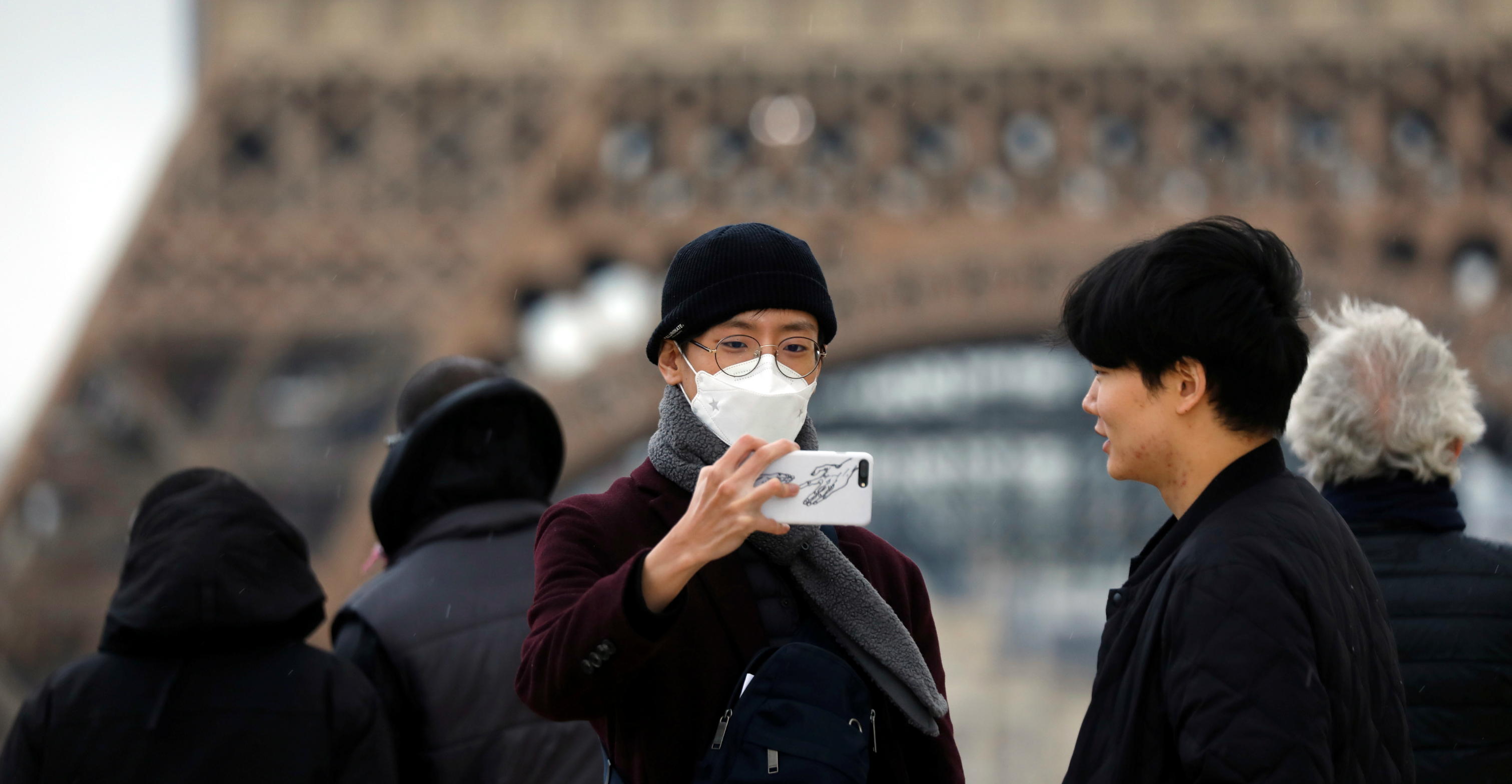 A man wearing a protective mask takes a selfie on the Trocadero esplanade in front of the Eiffel Tower in Paris on Wednesday. Photo: Reuters