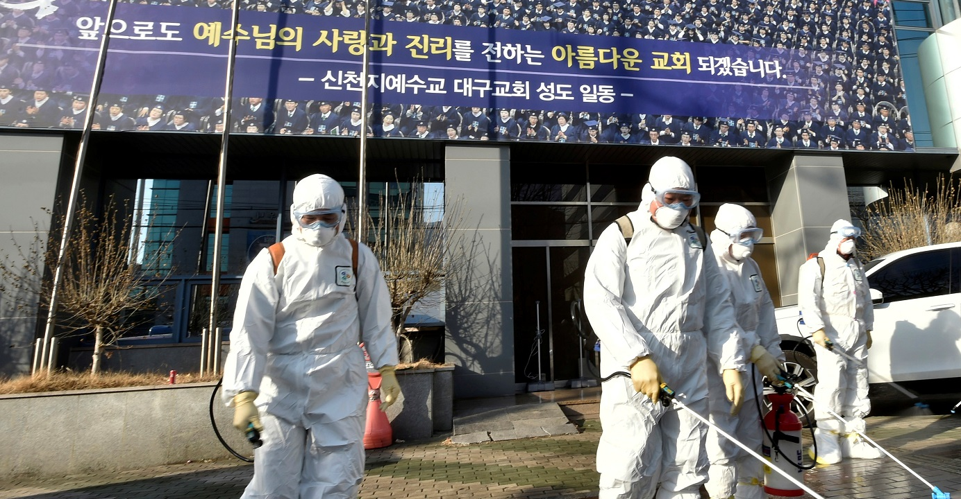Workers from a disinfection service company sanitize a street in front of a branch of the Shincheonji Church of Jesus in South Korea's Daegu city following multiple cases of coronavirus infection among the church-goers. Photo: Yonhap via Reuters