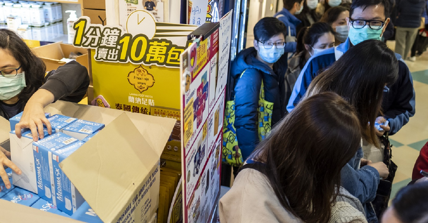 Customers wait in line as a store assistant unpacks boxes of protective masks at a Hong Kong shop. People must avoid buying into rumors about the virus epidemic, and should instead fight the outbreak with a rational mindset, the author says. Bloomberg