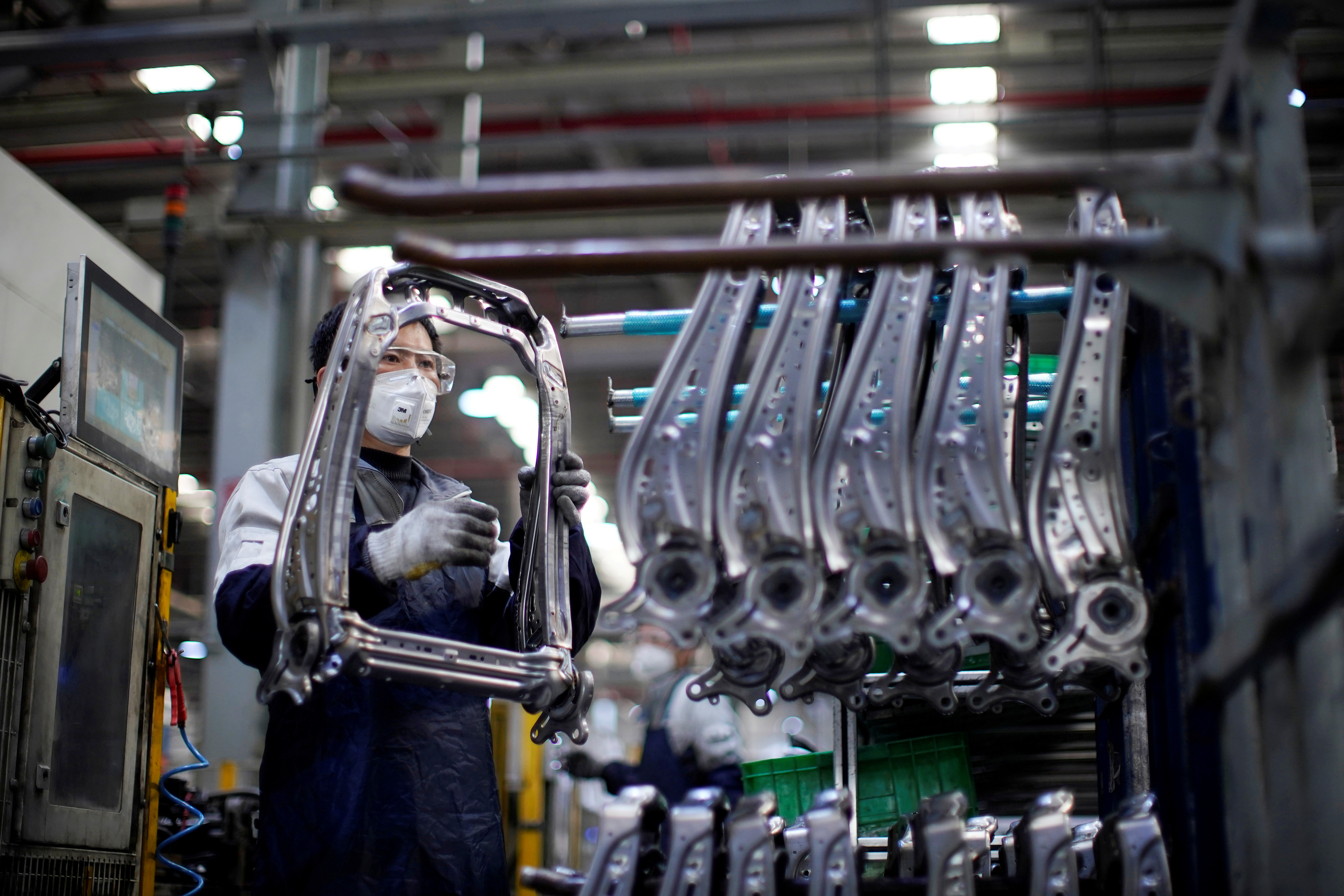 An employee wearing a face mask works on a car seat assembly line at a factory of Yanfeng Adient in Shanghai. Photo: Reuters
