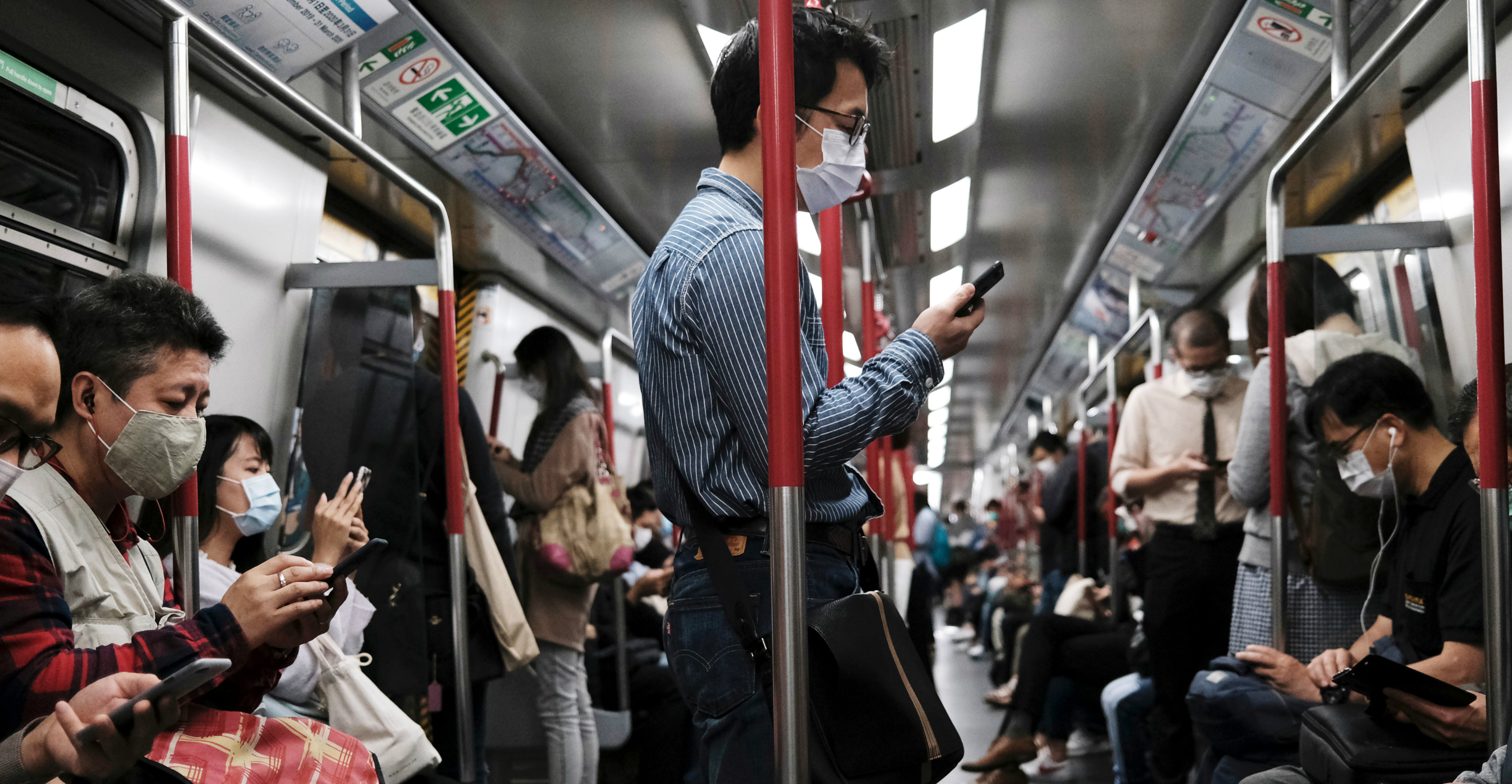 Passengers wear protective masks aboard an MTR train. Hong Kong people are more prepared to handle the coronavirus outbreak in view of their experience with the SARS epidemic in 2003. Photo: Reuters