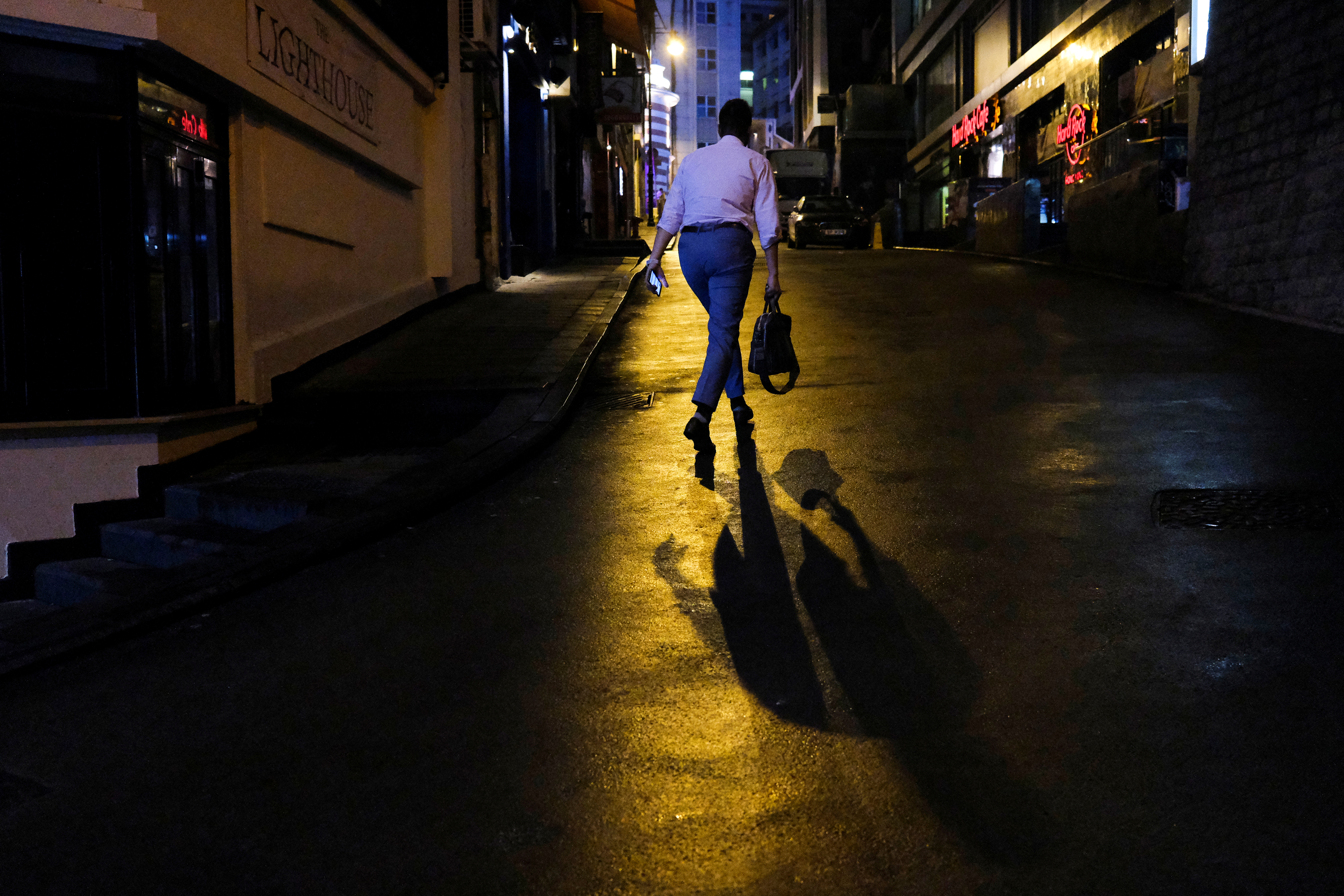 A person walks outside an almost empty pub area in Lan Kwai Fong on March 20 following the novel coronavirus outbreak. Authorities have reported more infections linked to popular nighttime activities in the area. Photo: Reuters